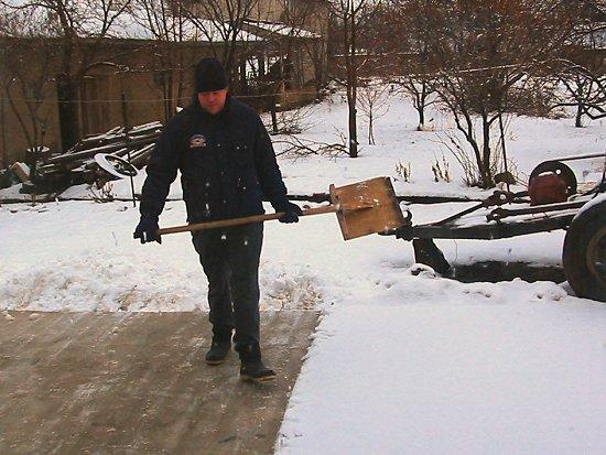 Sneeuwruimen van de betonnen oprit