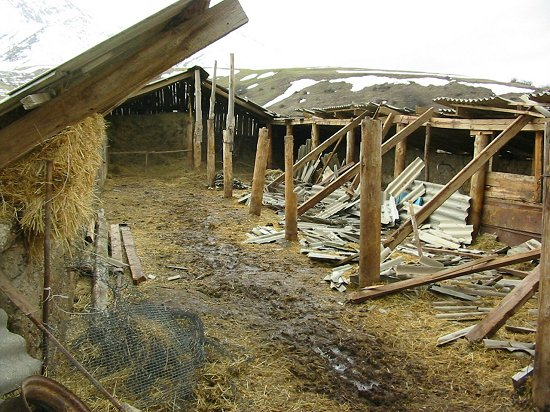 De restanten van de hooischuur na de instorting door overmatige sneeuwval